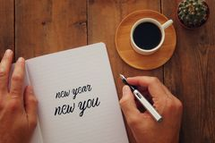 Top view of notebook and text NEW YEAR NEW YOU, cup of coffee over wooden desk. royalty free stock photo