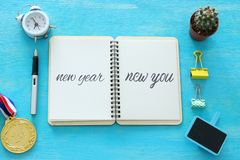 Top view of notebook and text NEW YEAR NEW YOU, cup of coffee over wooden desk. stock photo