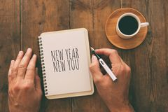 Top view of notebook and text NEW YEAR NEW YOU, cup of coffee over wooden desk. royalty free stock images