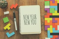 Top view of notebook and text NEW YEAR NEW YOU over wooden desk. royalty free stock photography