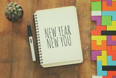 Top view of notebook and text NEW YEAR NEW YOU over wooden desk. royalty free stock photo
