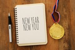 Top view of notebook and text NEW YEAR NEW YOU over wooden desk. stock images