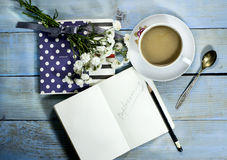 Top view of notebook on wooden table. With white flower and cup of coffee royalty free stock images