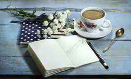 Top view of notebook on wooden table. With white flower and cup of coffee stock image