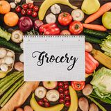 Top view of notebook with word grocery on vegetables and fruits. On wooden table Royalty Free Stock Images