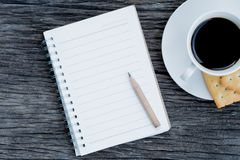 Top view of notebooks, pencils, coffee, biscuits on wooden stock image