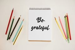 Top view of notepad with be grateful lettering and colorful pencils. Isolated on white Royalty Free Stock Photography