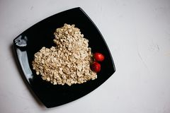 top view oat flakes in the form of a heart on a black plate and fresh strawberries royalty free stock photo