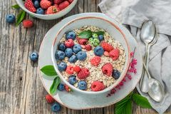 Top view of oat flakes with fresh blueberries and raspberries. On old wooden table Royalty Free Stock Photos