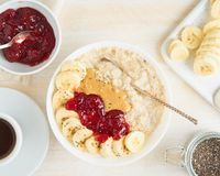 Top view of oatmeal porridge with strawberry jam, peanut butter, banana, chia on white wooden light background, healthy vegan stock photography