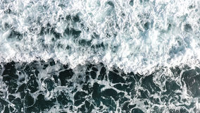 Top view of the ocean waves that crash against the rocky shore. stock photography