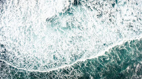 Top view of the ocean waves that crash against the rocky shore. stock images