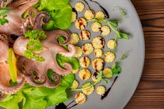 Top view of octopus served with lime, corn, cucumber and sprig o stock image
