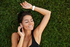 Free Top View Of A Satisfied Fitness Girl In Earphones Laying Royalty Free Stock Photography - 107565147