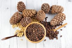 Top View Of A Set Of Cedar Cones And Pine Nuts With Wooden Spoons In A Wooden Bowl Stock Photos