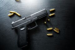 Free Top View Of Hand Gun On Black Background With Bullets Around. 9mm Pistol With Ammunition On Dark Table. Royalty Free Stock Photo - 187804235