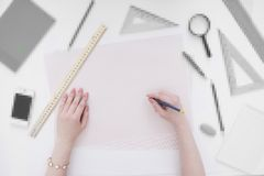 Top View Of Hand Holding Pen With School Supply Stock Images