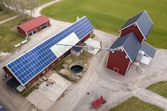 Top View Of Rural Landscape On Sunny Spring Day. Farm With Solar Photo Voltaic Panels System On Wooden Building, Barn Or House Stock Photo