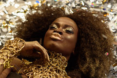 Top View Of Sensual Attractive Young Woman With Gold Lips Sending Air Kiss And Lying On Background Shining Confetti Stock Photos