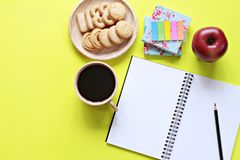 Free Top View Of Working Desk With Blank Notebook With Pencil, Cookies, Apple, Coffee Cup And Colorful Note Pad On Yellow Background Royalty Free Stock Image - 84119616