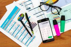 Top view of office desk with data chart and smart phone. Open calculator app Royalty Free Stock Images