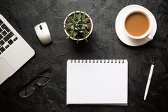 Top view of office desk. Green plant in a pot, cup of coffee, computer mouse, pen, modern silver laptop with blank notepad for. Your text on dark background royalty free stock images