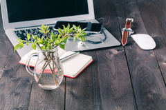 Top view office desk mockup. Laptop, flower, and cup of tea on rustic wooden background stock photos