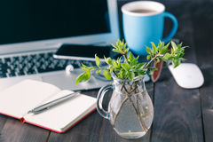 Top view office desk mockup. Laptop, flower, and cup of tea on rustic wooden background stock photography
