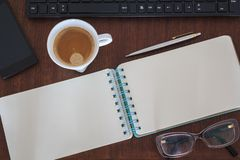 Top view of Office desk with notebook, computer, coffee cup, smartphone and glasses.  stock photos