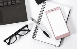 Top view office desk. Smartphone laptop pen notebook and glasses on white background Stock Photos