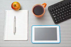 Top view of office desk with tablet pc with notebook , keyboard. And cup of tea royalty free stock photography