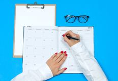 Top view office desk.  Workspace with female hands, clipboard, calendar and glasses. Top view office desk. Woman writing on calendar.  Workspace with female Royalty Free Stock Images