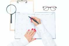 Top view office desk.  Workspace with female hands, clipboard, calendar and glasses. Top view office desk. Woman writing on calendar.  Workspace with female Royalty Free Stock Photos