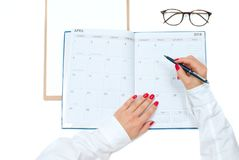 Top view office desk.  Workspace with female hands, clipboard, calendar and glasses. Top view office desk. Woman writing on calendar.  Workspace with female Stock Photography