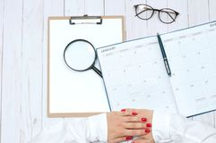 Top view office desk.  Workspace with female hands, clipboard, calendar and magnifier. Top view office desk. Calendar.  Workspace with female hands, clipboard Royalty Free Stock Photography