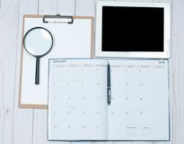 Top view office desk.  Workspace with female hands, clipboard, calendar and tablet. Top view office desk. Calendar.  Workspace with female hands, clipboard Stock Image