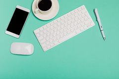 Top view of office desk workspace with smartphone, keyboard, coffee and mouse on blue background with copy space, graphic designer stock photography