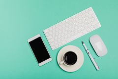 Top view of office desk workspace with smartphone, keyboard, coffee and mouse on blue background with copy space, graphic designer. Creative Designer concept stock photo