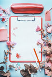 Top view of office table desk with clipboard ,accessories and flowers on blue background,frame. . Workspace. Flat lay Stock Photo