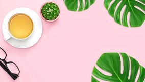 Top view, office table desk with copy space. Workspace frame with green tropical leaf and tea cup, cactus, on blue pink background. Top view, office table desk stock photography
