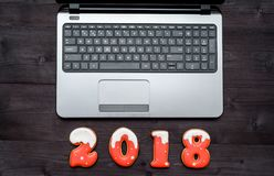 Top view of office table desk with open laptop and new year 2018 sign symbol from gingerbread cookies. Business holidays concept. Workspace with laptop and Royalty Free Stock Photos