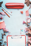 Top view of office table desk. Workspace with pen,clipboard ,accessories and flowers on blue background. Frame Royalty Free Stock Photo