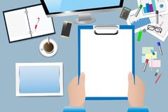 Office workplace concept vector. Top view of the office table. Hand is holding empty notepad ready for your text Royalty Free Stock Photos