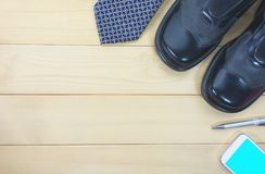 Top view office table with necktie, work shoes, smart phone royalty free stock photo