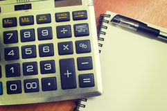 Top view of an office wooden desktop with calculator and pen Royalty Free Stock Photos