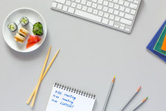 Top View Office Work Place on grey Desk Sushi Schedule. Top View of Office Work Place on grey Table with Computer Pencils Documents and Sushi Set with wooden stock photo