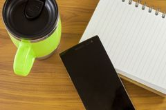 Top view of office work place, note book ,glass and smart phoned. On the wooden table Stock Photo