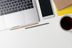 Top view of office workplace. White desk with copy space. Flat lay view on table with laptop, pen, phone, pencil, notebook. And black coffee. Creative designer stock photo