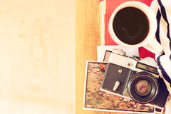 Top view of old camera, cup of coffe and stack of photos. filtered image. travel or vacation concept Royalty Free Stock Photo
