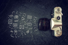 Top view of old camera over blackboard and infographics sketches.  Royalty Free Stock Photos